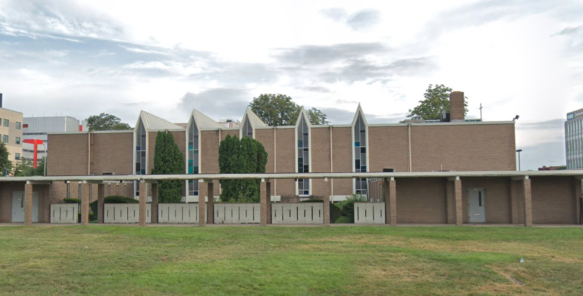 The exterior of the Friendship Baptist Church in Detroit. The facade is brown with stained glass windows.