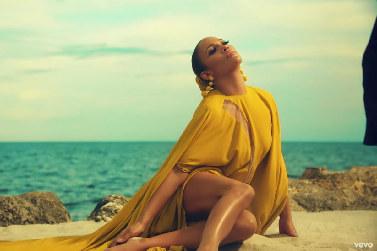 A screenshot from Jennifer Lopez's new video that was filmed at the Zim Estate in the Florida Keys. J-Lo is wearing a bright yellow dress with the ocean behind her.