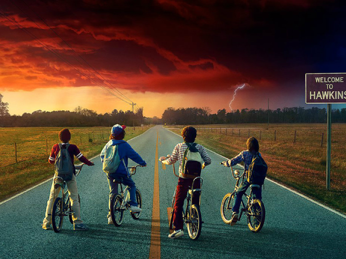 """""""Stranger Things 2"""" promo image of four boys on bikes, stopped on a paved road, looking at a threatening cloud on the horizon"""
