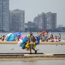 A man sells balloons as people cool off at Montrose Beach on the North Side during a heat wave, Friday afternoon, July 19, 2019.