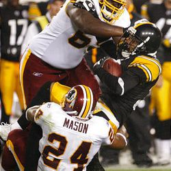 Pittsburgh Steelers cornerback Keiwan Ratliff is stopped by Washington Redskins offensive lineman Rueben Riley and Washington Redskins running back Marcus Mason after an interception.