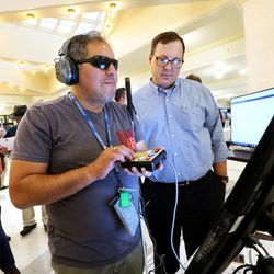 Nick Rios, who is visually impaired, tries out Clear Ballot's voting system as the company's Chris Hanna looks on at the state Capitol in Salt Lake City on Wednesday, Aug. 2, 2017. Members of the public will be able to try out five different machines the state is considering buying.