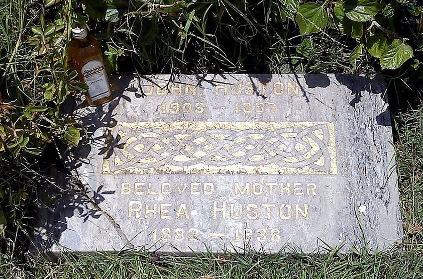 A grey headstone in Hollywood Forever cemetery. The words on the headstone read: John Huston, beloved mother Rhea Huston. There is a bottle of liquor sitting against the headstone.
