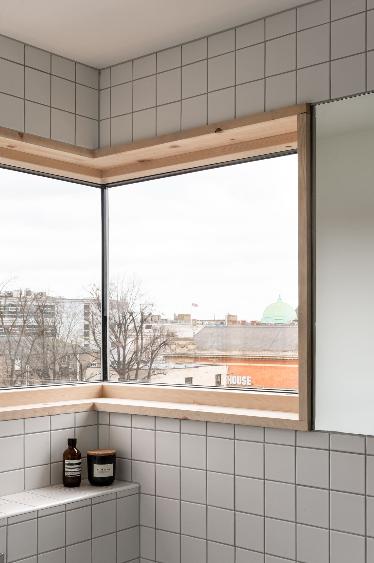 Corner of a bathroom with grid tiles and windows.