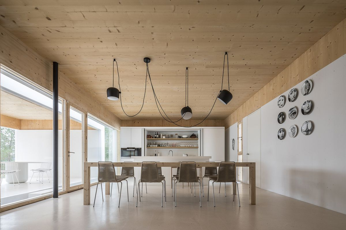 Kitchen with modern pendant lamp hanging over table.