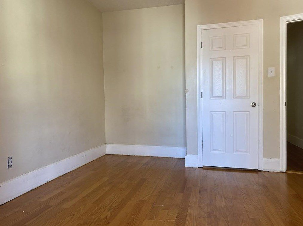 An empty room with a closed closet door.