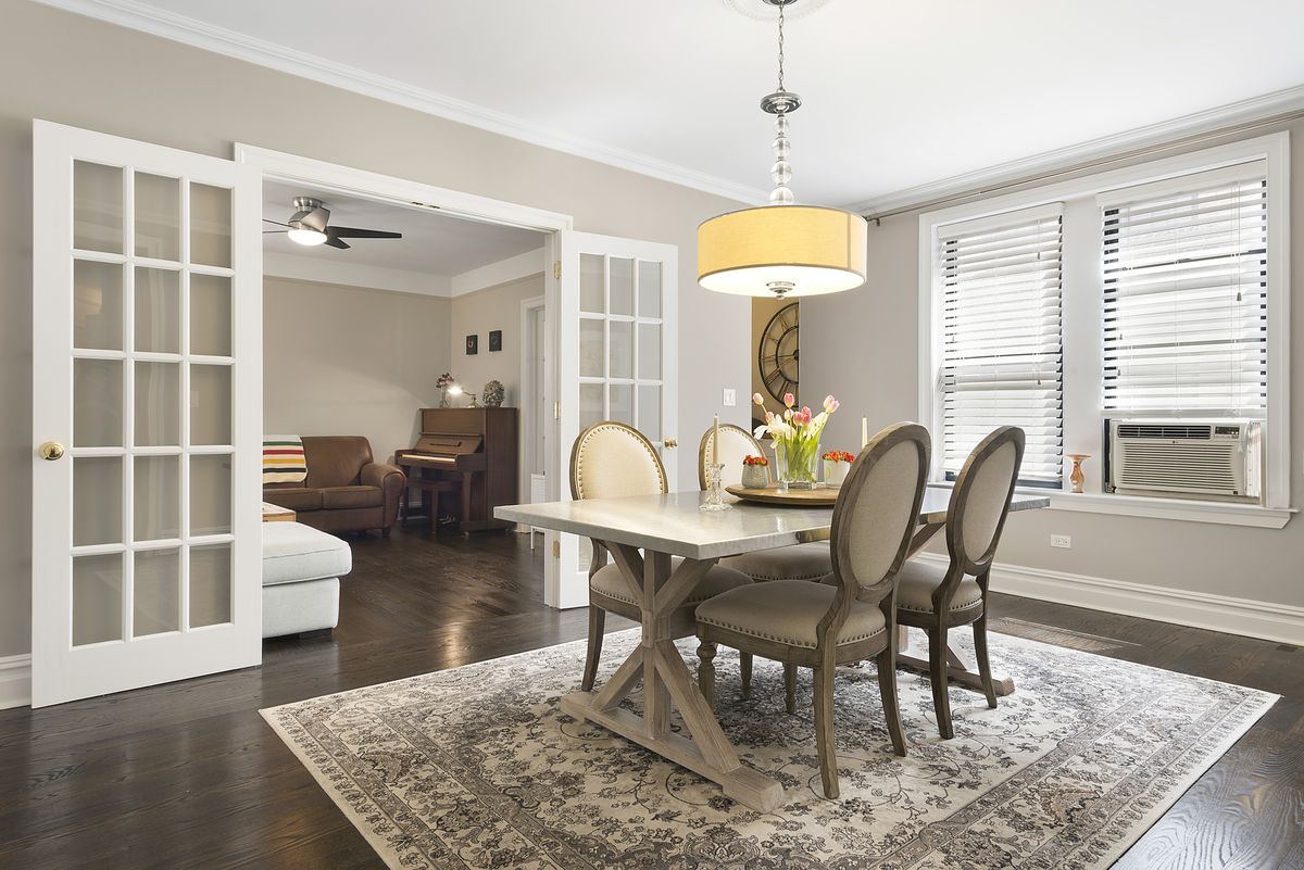 A dining area with hardwood floors, beige walls, crown moldings, a table with four chairs, and a rug.
