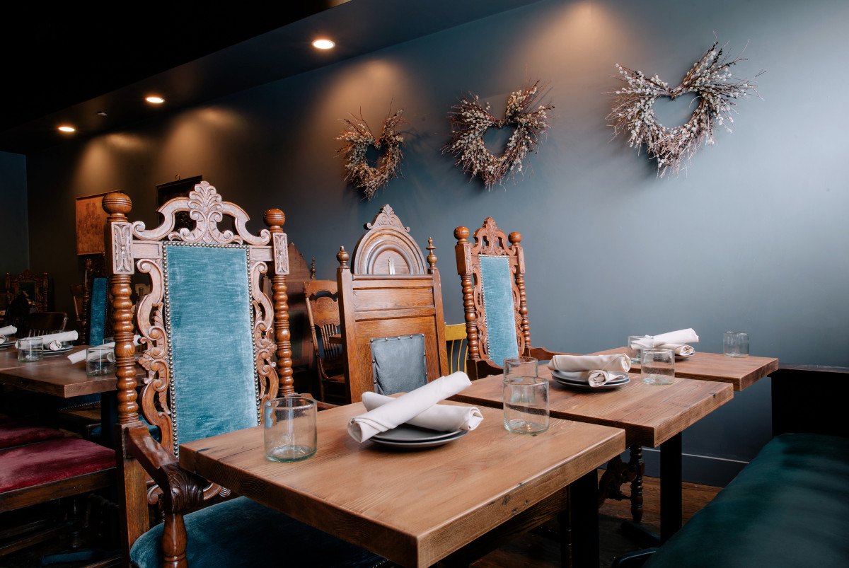 Finely carved wooden chairs with plush blue velvet padding line opposite wooden tables with a light blue wall in the rear at Bronwyn in Somerville.