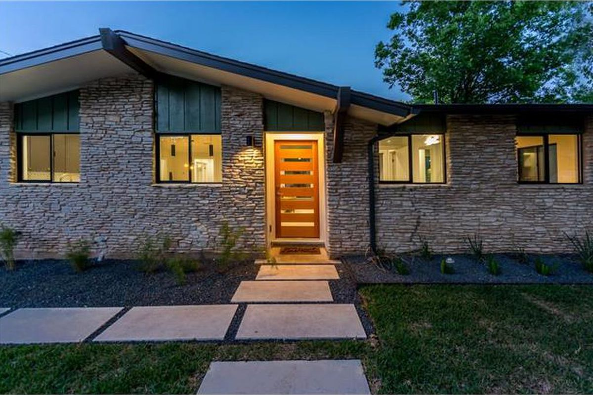 Midcentury ranch house with peaked front roof, brick, at dusk