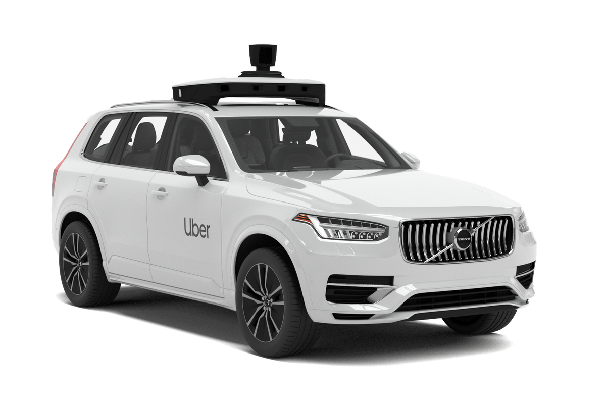 A white SUV Volvo with a camera on top.