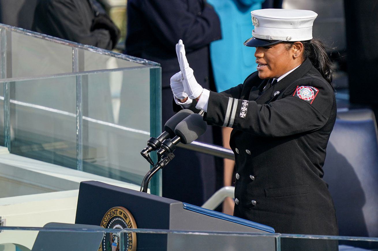 A Black woman in uniform stands at a podium, holding up her hands in the middle of signing.
