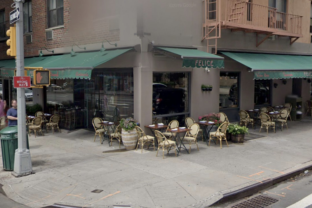 The exterior of a restaurant with green awnings on the corner of a block with a wide expanse of sidewalk out front and tables and chairs set up outdoors under the awnings