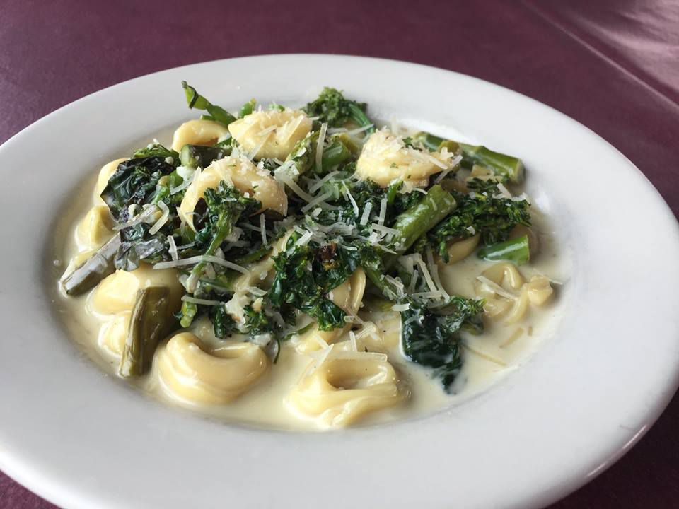 A plate of tortellini with spinach and cream sauce