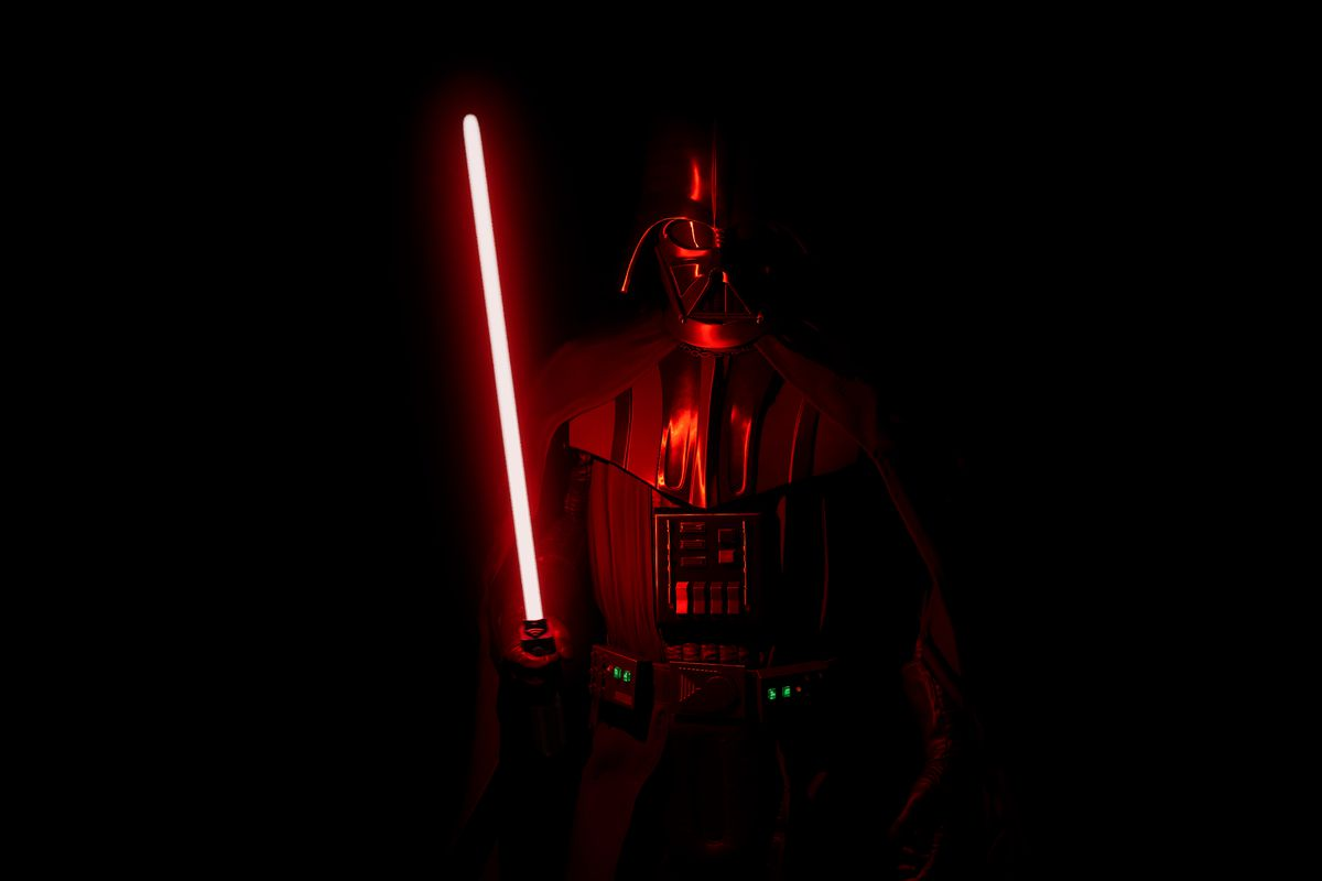 Darth Vader stands in a dark room