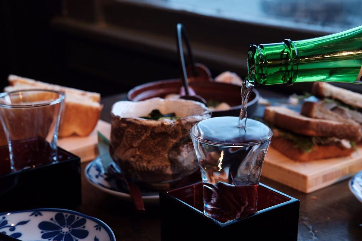 Sake being poured from a bottle into a small shot glass, with snacks in the background.