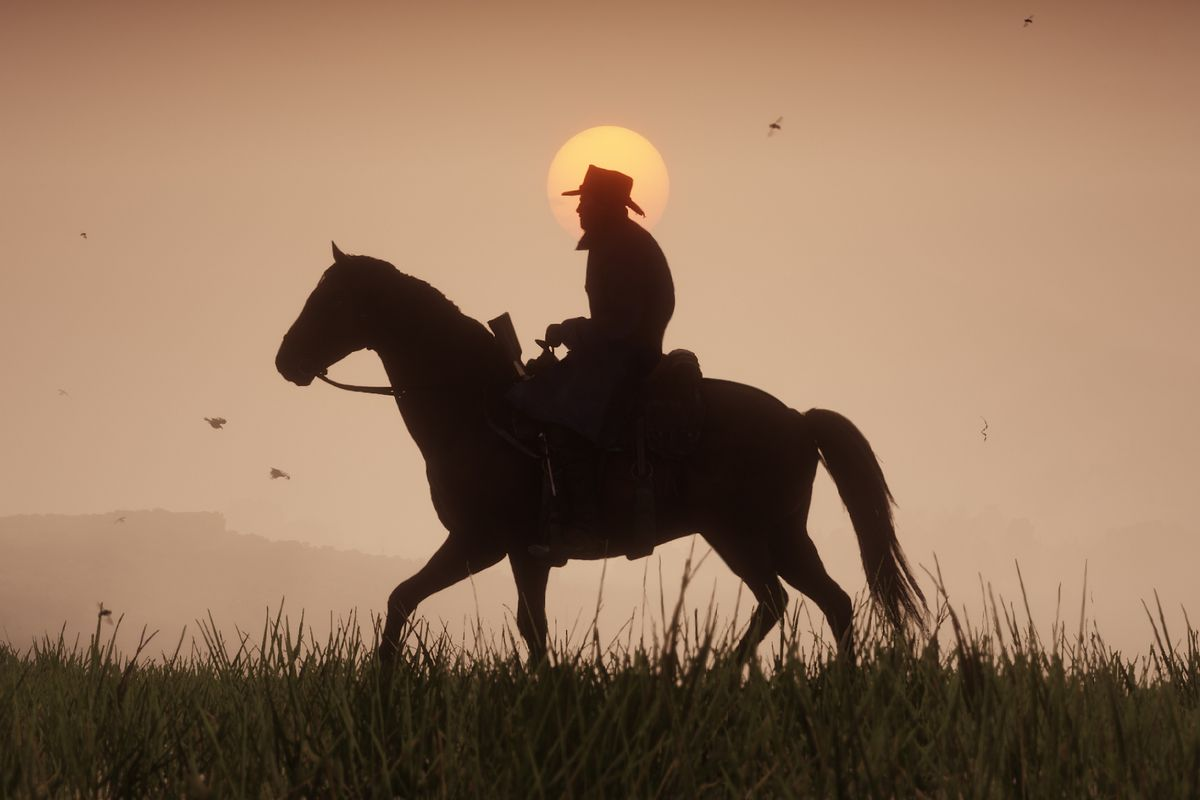 Red Dead Redemption 2 - silhouette of man on horseback with sunset in the background