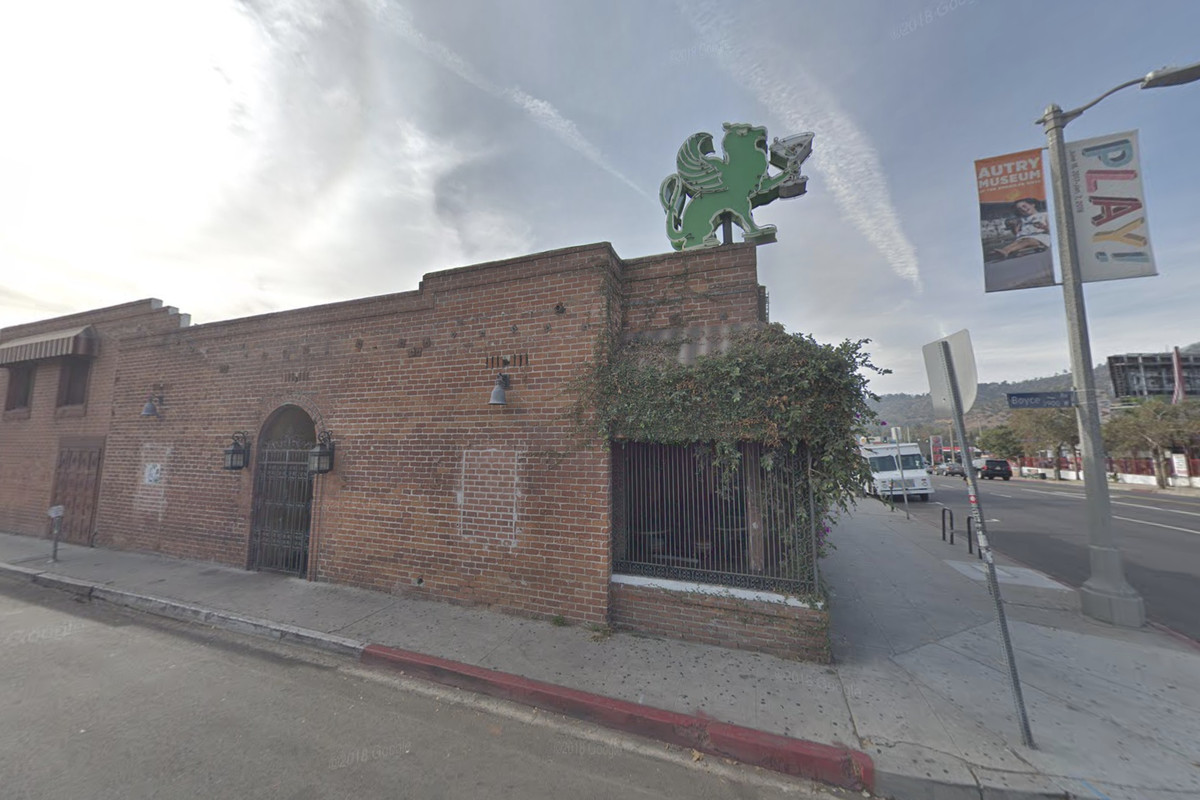 The Griffin, a brick dive bar on a bright corner, as seen from the street.
