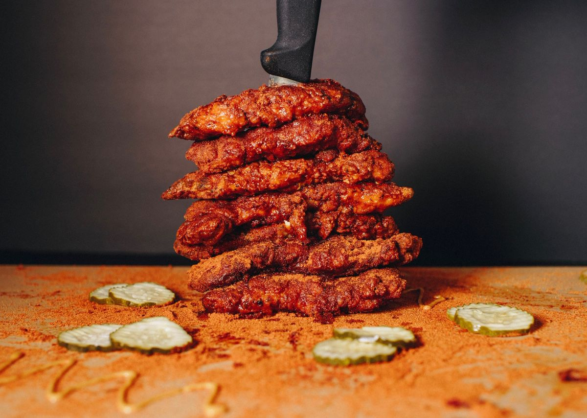 A stack of spicy chicken tenders with a knife through the top.