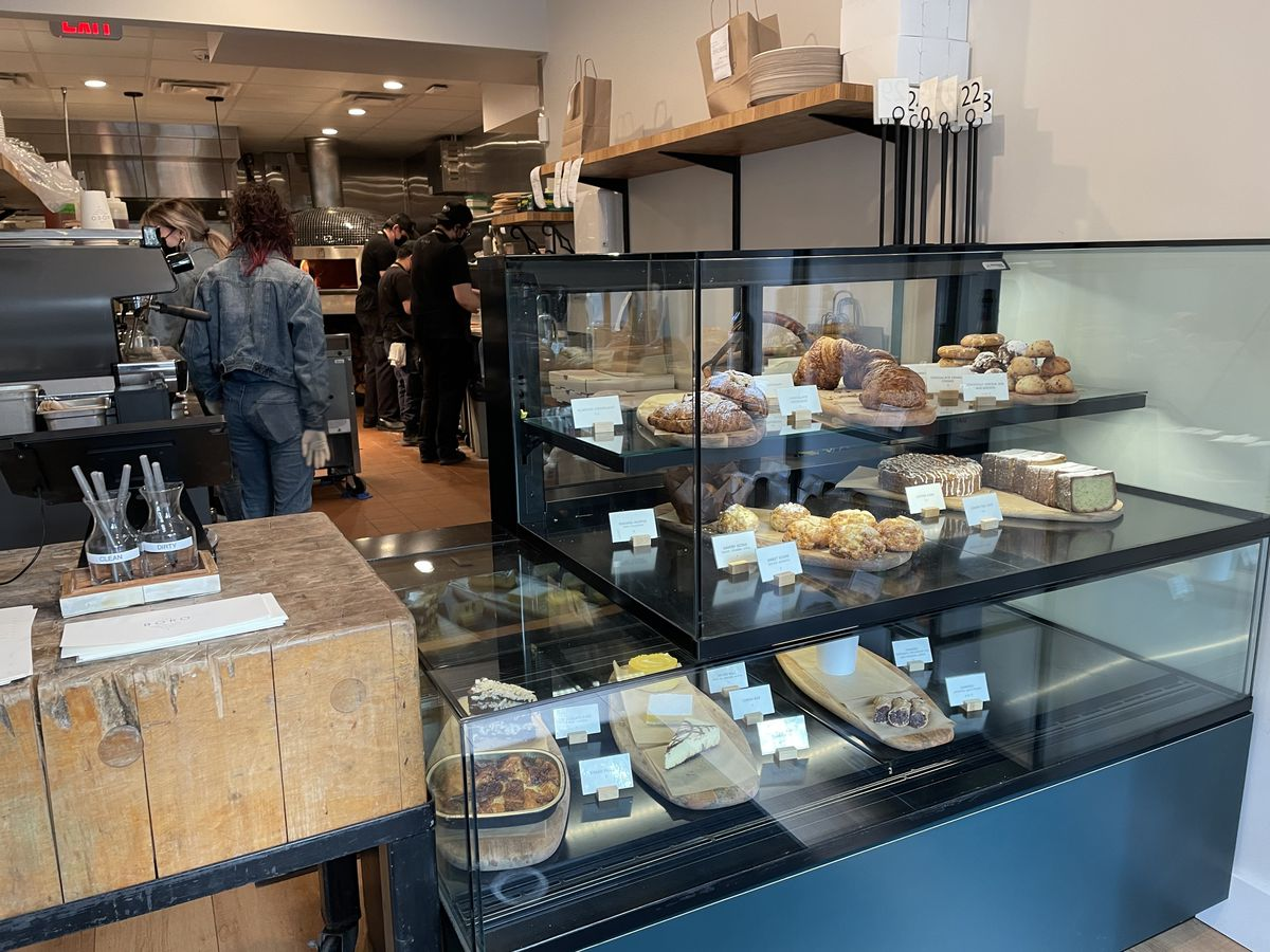 People work behind the counter of the Boro To Go. A three-tier case displays pastries and cheeses