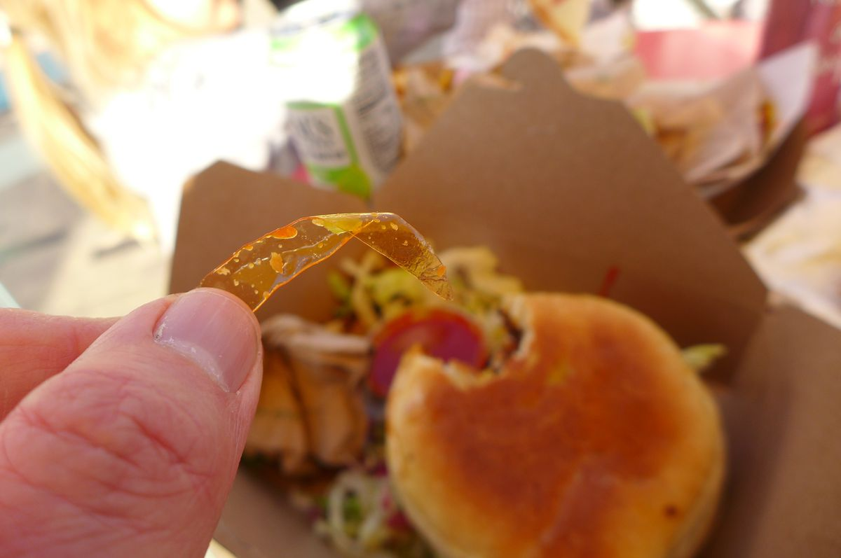 A hand holds a piece of plastic over a bun with a bite taken out of it.