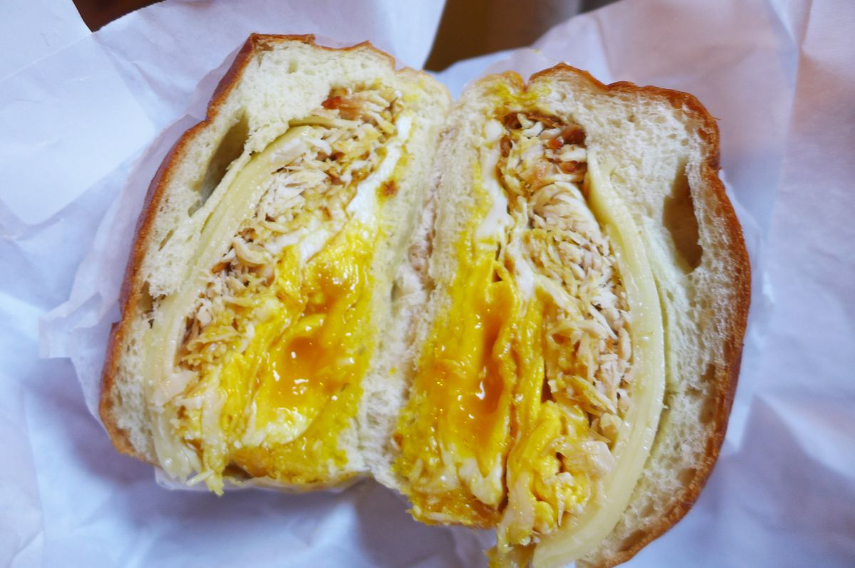 A sandwich with runny egg, turkey, and white cheese but in half and cradled in white butcher paper.