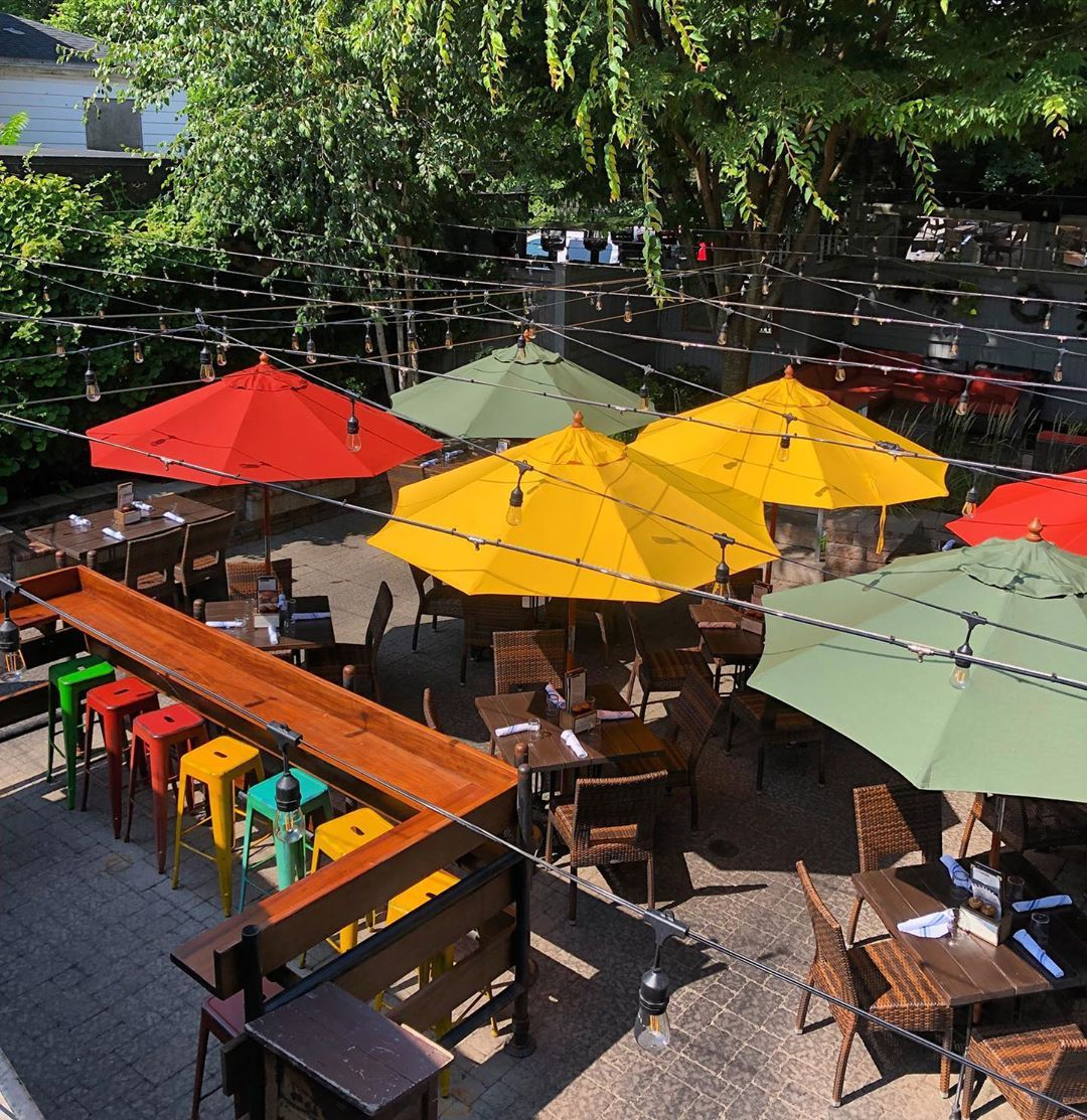 An outdoor dining patio at a restaurant, featuring a dark wooden deck and colorful umbrellas and metal stools in red, green, and yellow