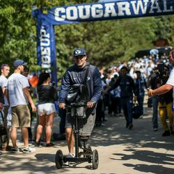 Brigham Young Cougars quarterback Tanner Mangum (12), injured in last week's game against Utah, wheels into LaVell Edwards Stadium on a scooter before the game against the Wisconsin Badgers in Provo on Saturday, Sept. 16, 2017.