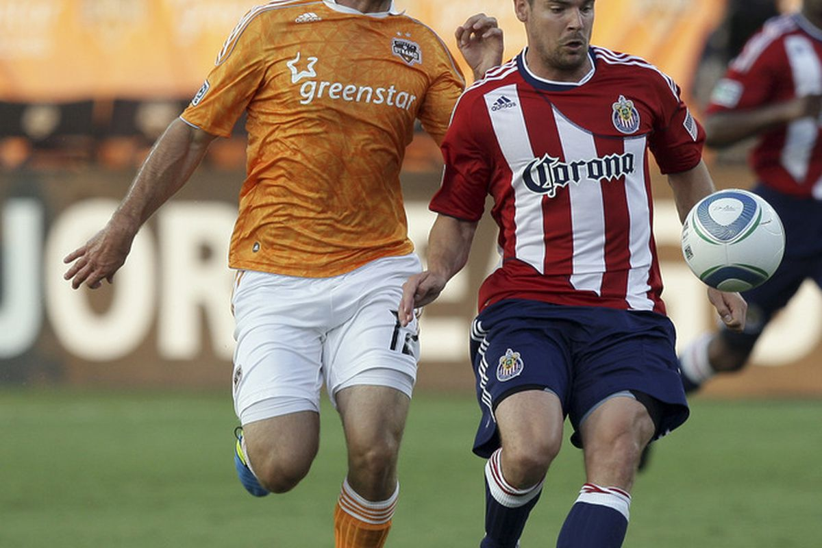 HOUSTON - JUNE 11:  Heath Pearce #3 of Chivas USA and Will Bruin #12 of the Houston Dynamo fight for possession of the ball during the first half at Robertson Stadium on June 11, 2011 in Houston, Texas.  (Photo by Bob Levey/Getty Images)