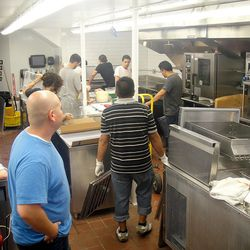 Chef Abrams (left) watches the crew work furiously.