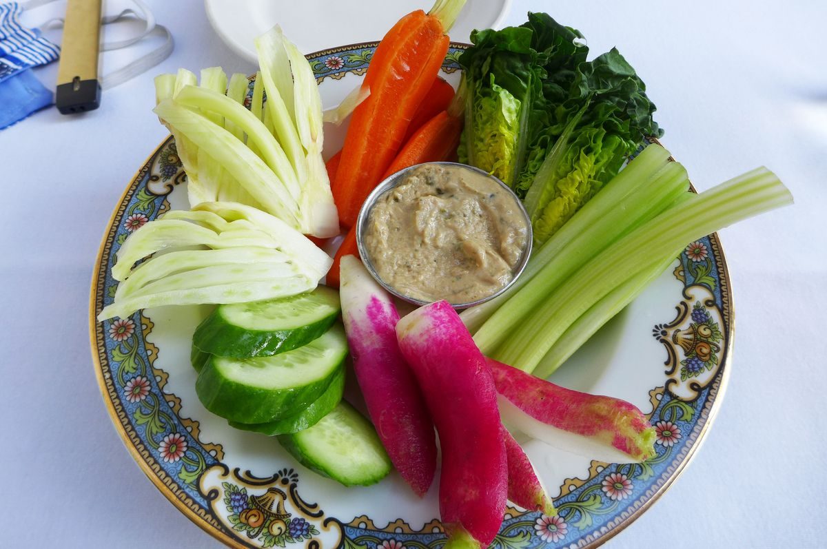 Crunchy vegetables including long red radishes and white fennel fanned around a small dish of brown dip.