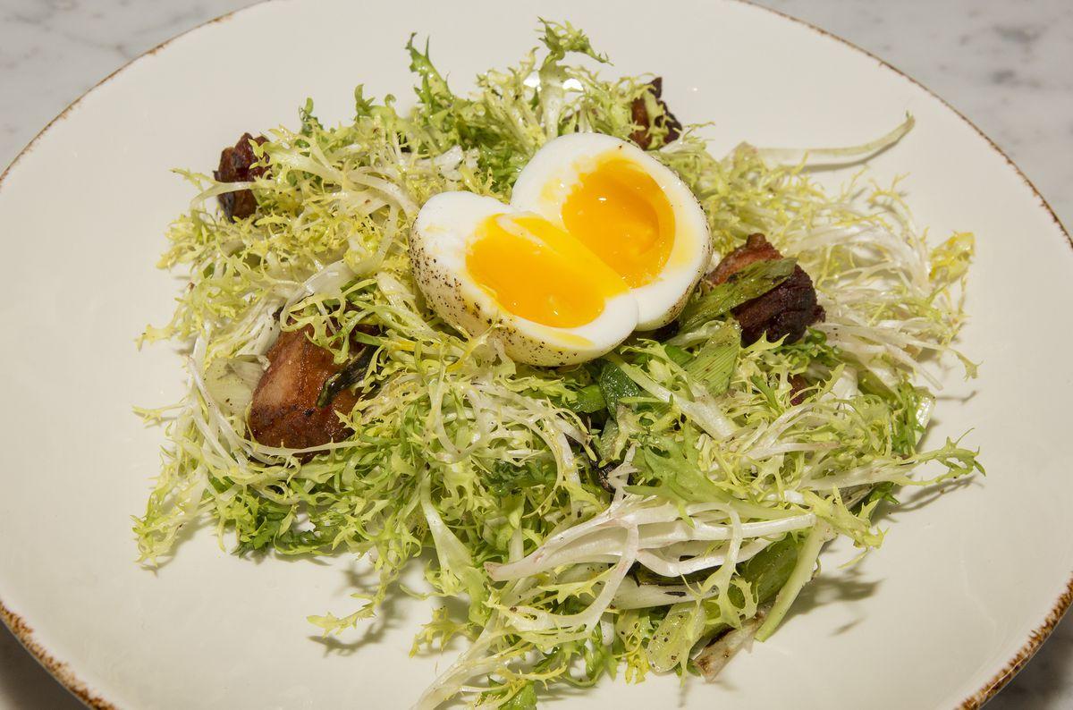 A salad with bacon lardons and soft egg