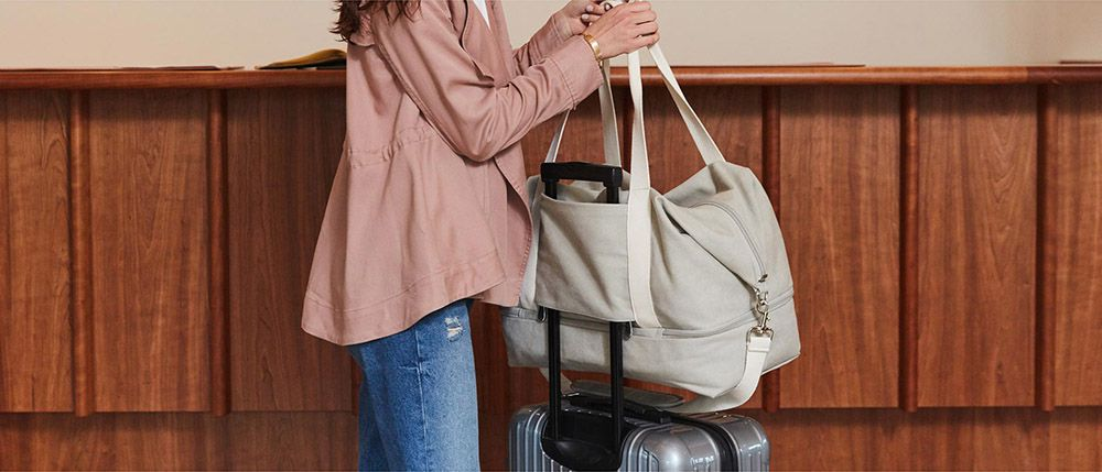 c1d66369d708 A woman with a canvas carry on bag Photo  Lo   Sons
