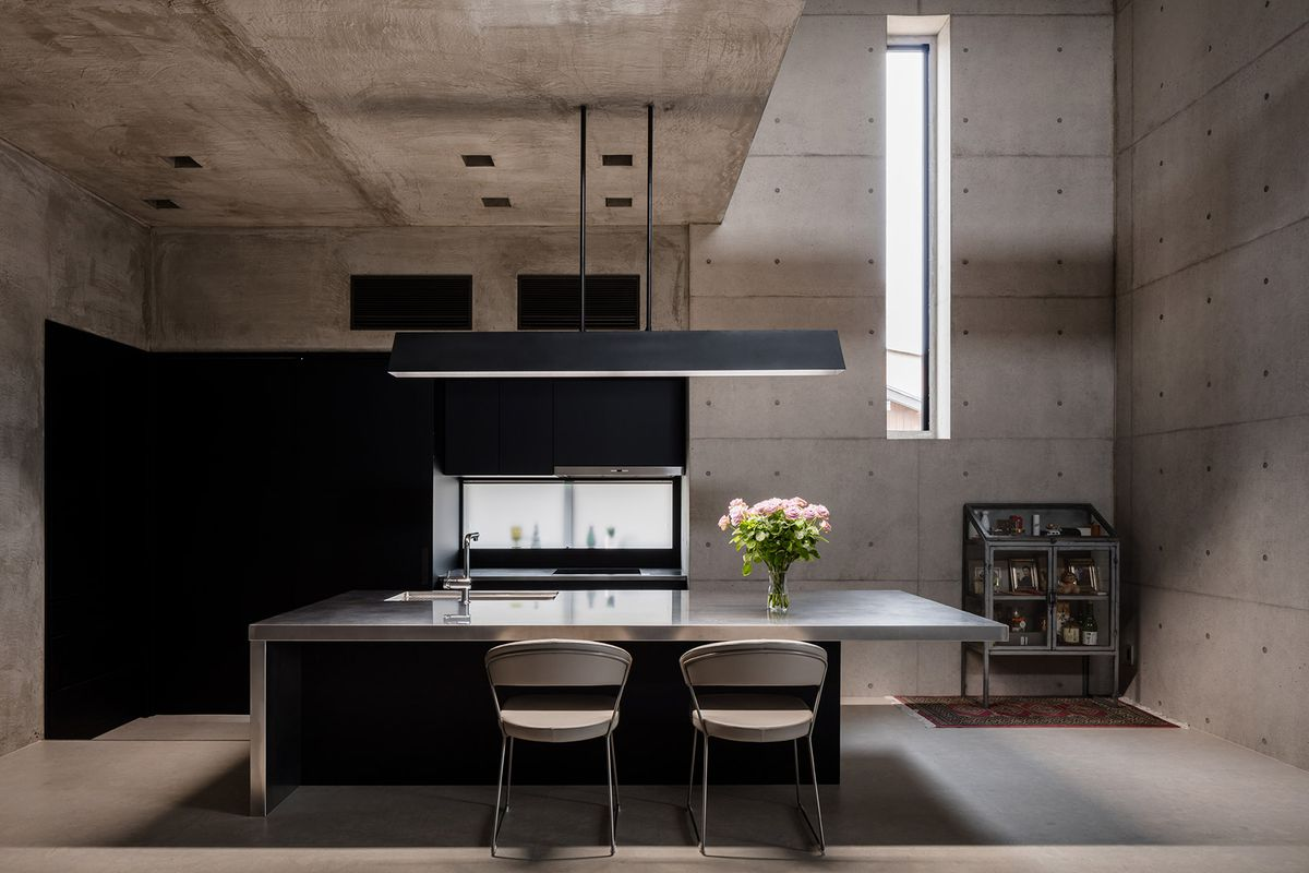 A dining area with concrete walls and floors. There is a table, chairs, and a small display dresser.