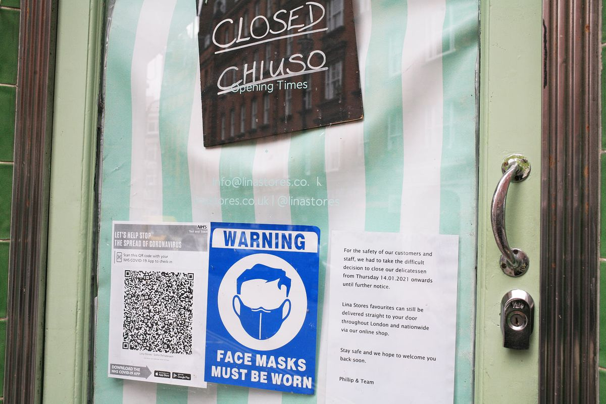 Covid-19 signage at Lina Stores during lockdown in early 2021, with a QR code and blue mask sticker on the door of the restaurant