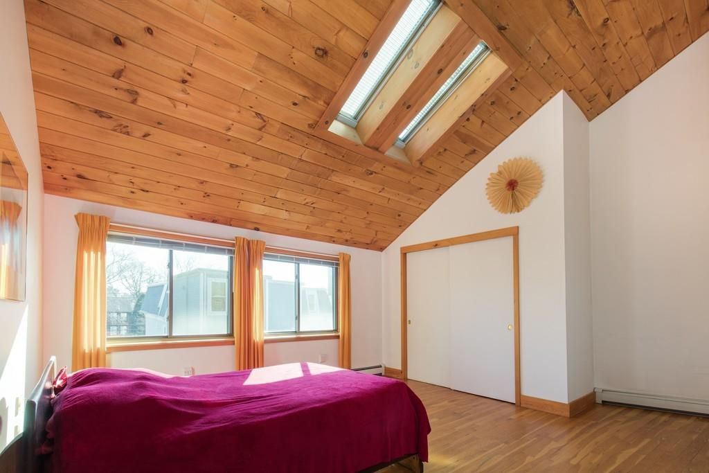 An open, loft-like bedroom with a bed and two skylights.