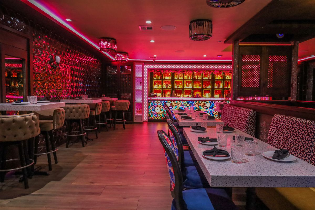 A neon pink lighted dining area with banquette and bar height seating at Mama Por Dios.