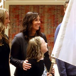 Water polo olympian Courtney Young Johnson laughs with her children Ainsley Johnson, Ammeline Johnson and Maddox Johnson, behind the flag, before being honored at the Utah Sports Hall of Fame banquet at the Little America Hotel in Salt Lake City on Monday, Sept. 20, 2021.
