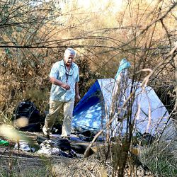 Ed Snoddy searches for his friends in a camp near the Jordan River in Salt Lake City on Tuesday, Nov. 15, 2016.