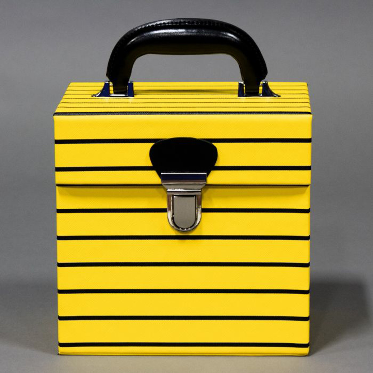 A yellow box with black stripes, a black handle, and a black lock mechanism.