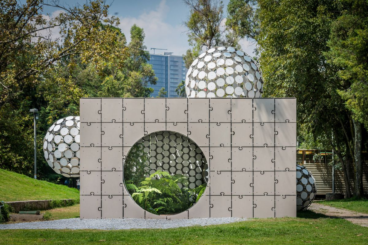 Pavilion made of a wall of concrete with a round entrance filled with plants.