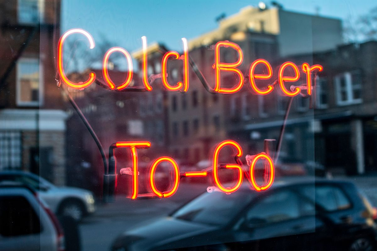 """Stock photograph of a neon sign in a window that reads """"Cold Beer to Go"""" in red"""