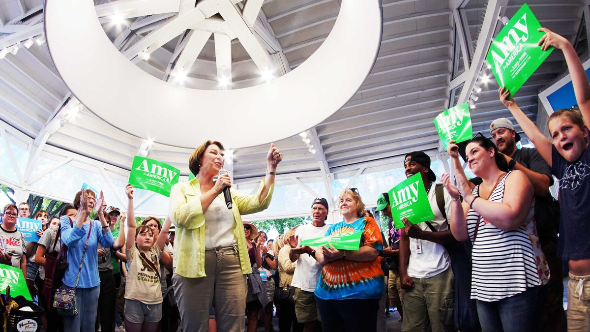 "Amy Klobuchar speaks on a microphone in front of a large crowd holding up signs that ready ""Amy."""