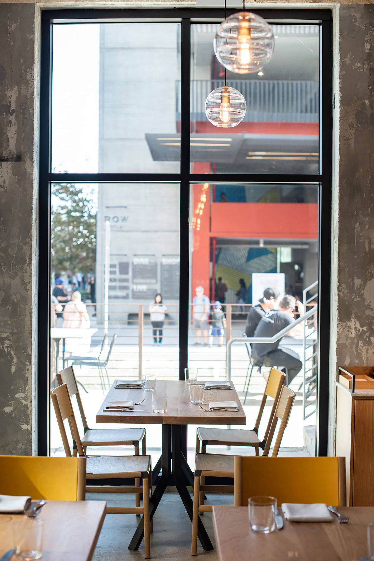 Tall windows at a new warehouse restaurant with yellow wooden chairs.