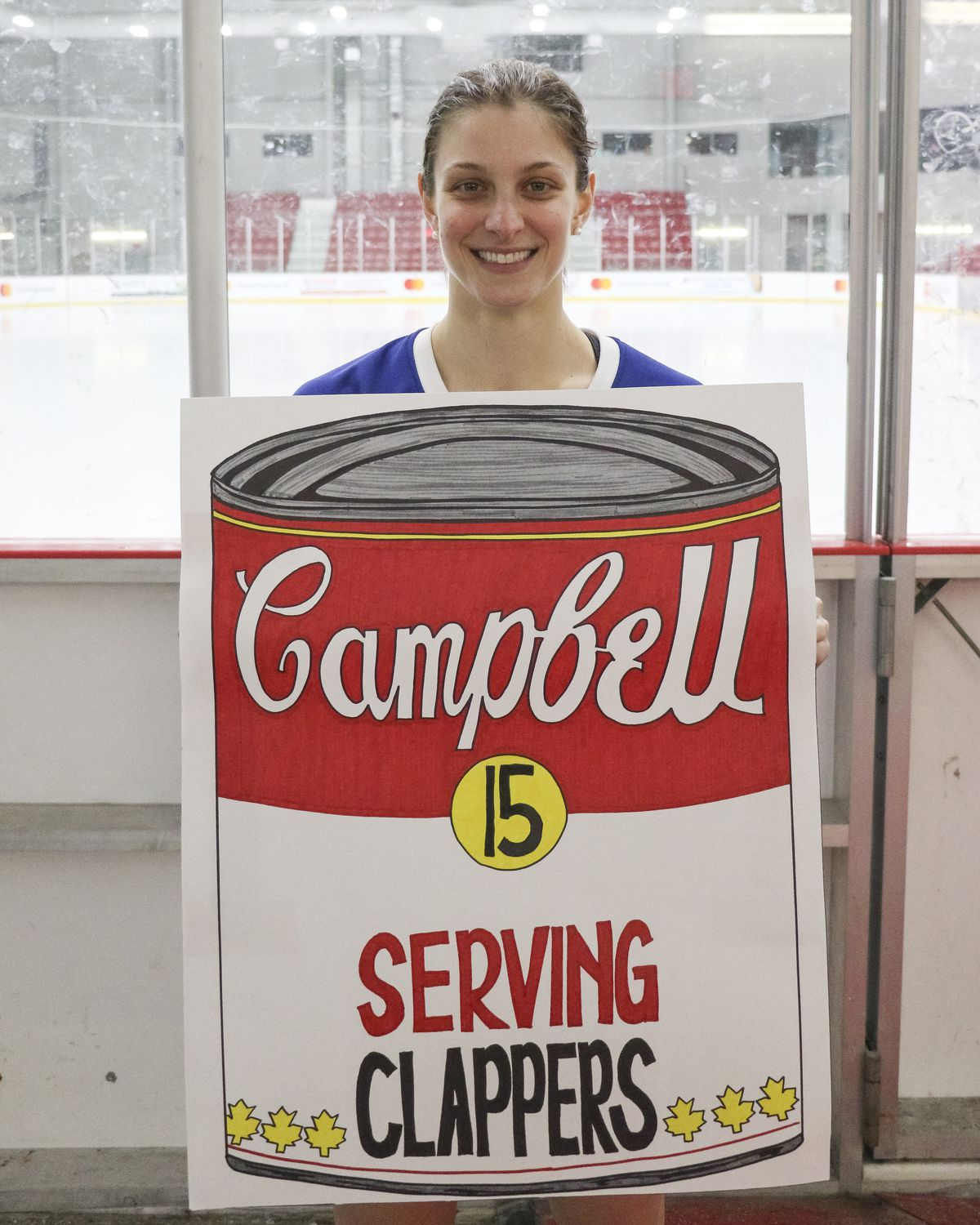 """Carlee Campbell holding a sign showing a tin of Campbell's soup that reads """"Campbell 15 SERVING CLAPPERS"""""""