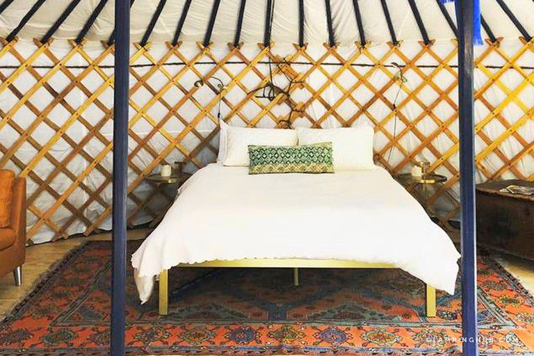 The interior of a tent with a curved cloth wall and ceiling supported by a crisscrossed wood frame and bars extending to top of circular ceiling and two floor-to-ceiling support poles. There'sa . simple platform bed with comforter and pillows and two nightstands on a rug, centered behind the poles.