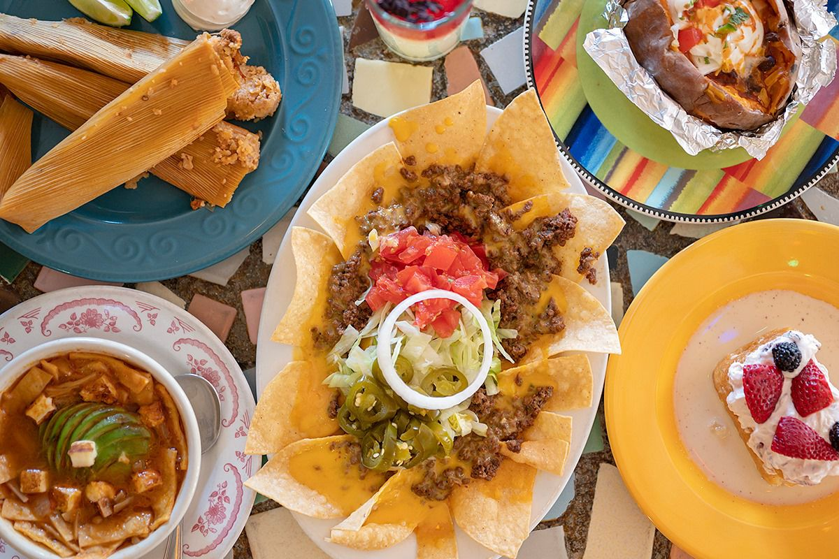 an overhead shot of a spread of tex-mex food, including enchiladas, tamales and tortilla soup