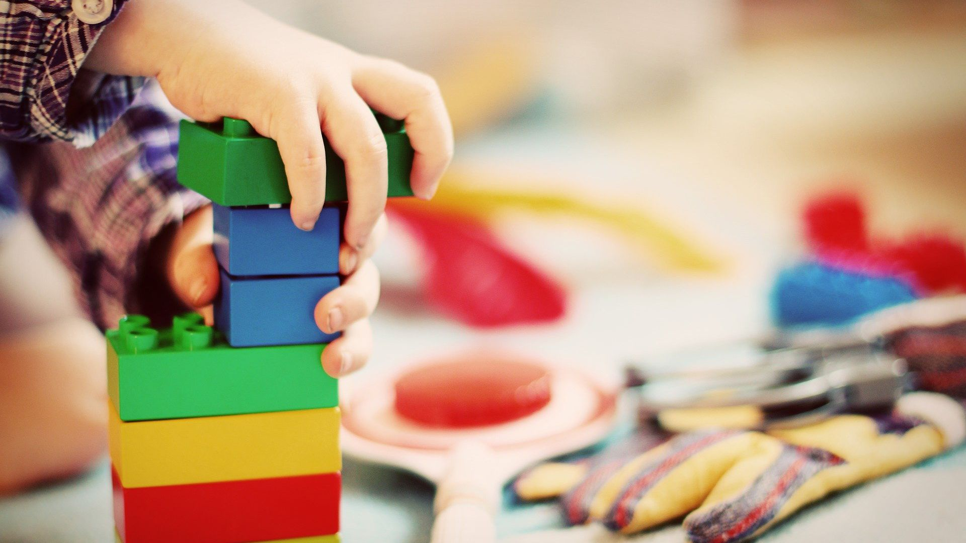 Close-up of a child's hands building with Legos.