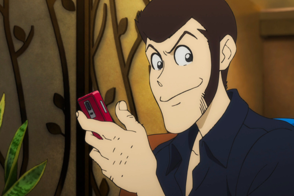 Lupin III smiling and holding a red cell phone.