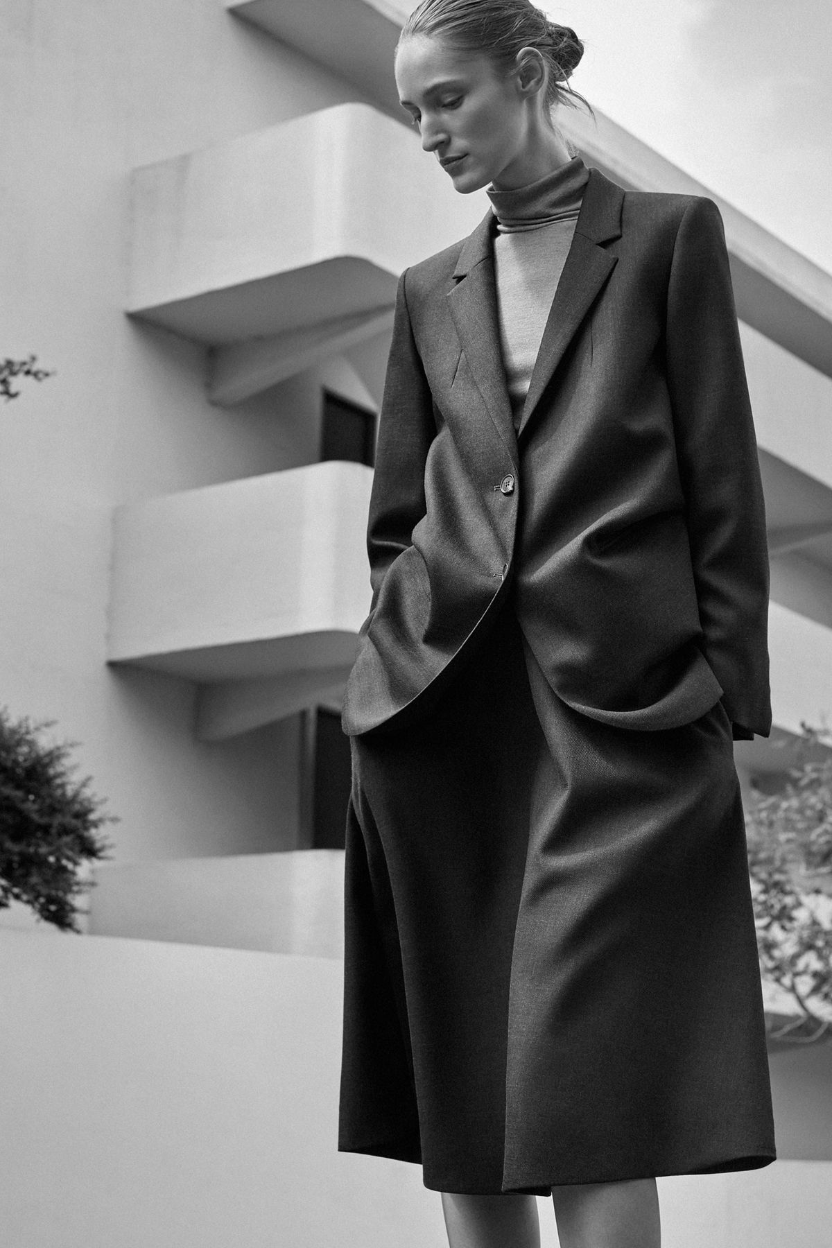 A woman wears an oversize blazer over a turtleneck, and loose-fitting cropped pants underneath.