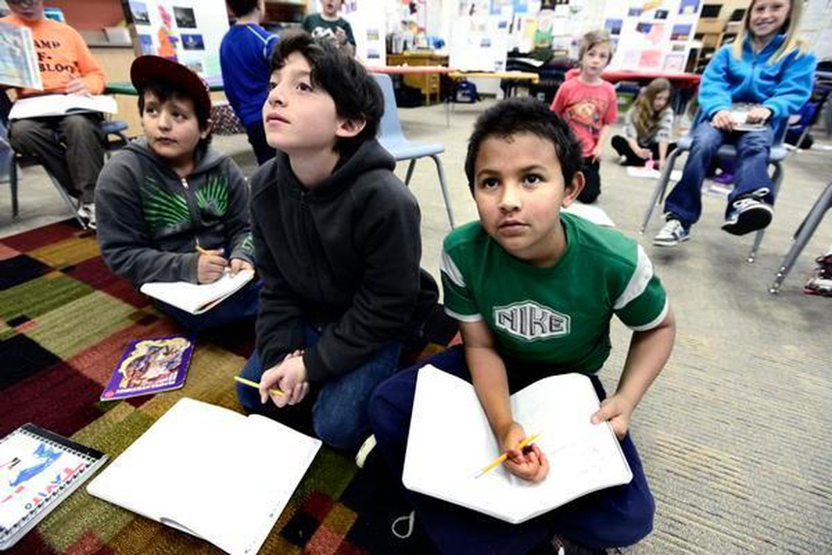 From left to right Harian Aldama, Miguel Silva, and Julian Aldama look over a reading and writing lesson on the classroom board in Jessica Cirelli's third-grade class at Escuela Bilingue Pioneer Elementary in Boulder on Tuesday morning May 7, 2013. (Denver Post file)